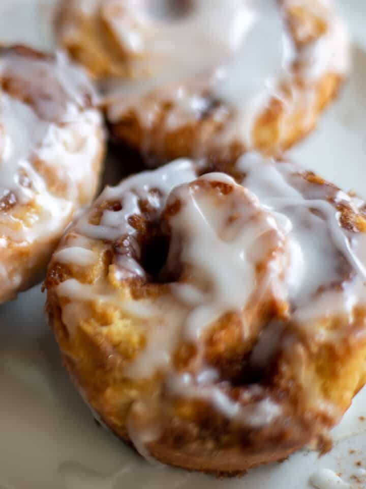 Close up image of three cinnamon rolls on a white plate.