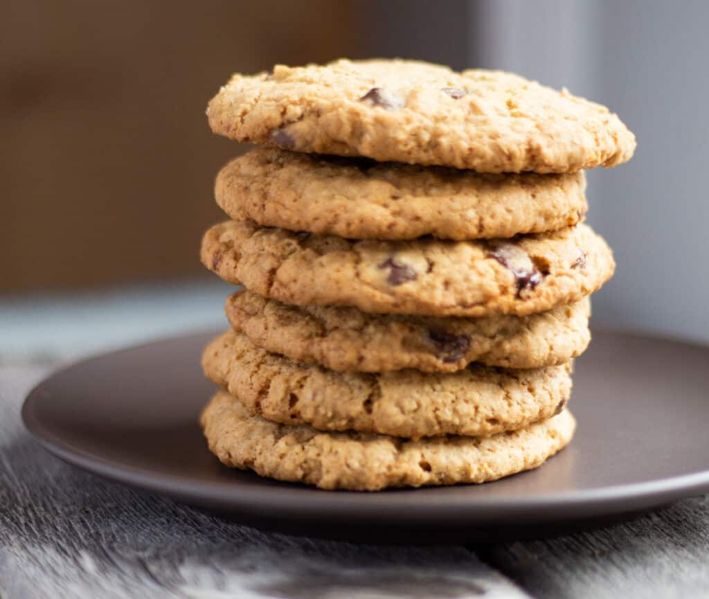 six oatmeal chocolate chunk cookies stacked on a plate