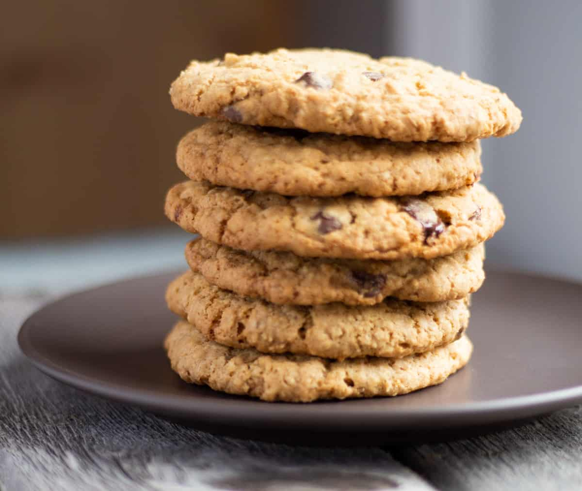Six oatmeal chocolate chunk cookies stacked on a plate.