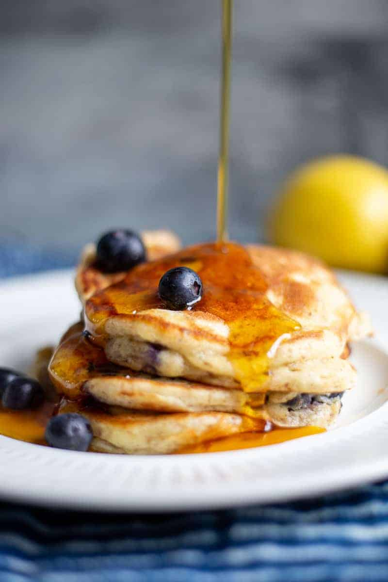 Lemon blueberry pecan pancakes on white plate with maple syrup being drizzled on top.
