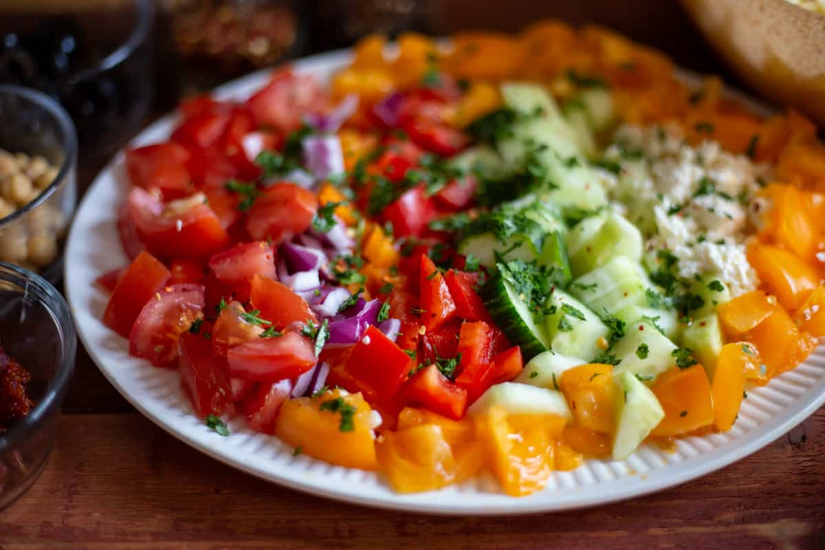 chopped tomatoes, red onions, red and yellow peppers, fresh chopped parsley and basil on white plate