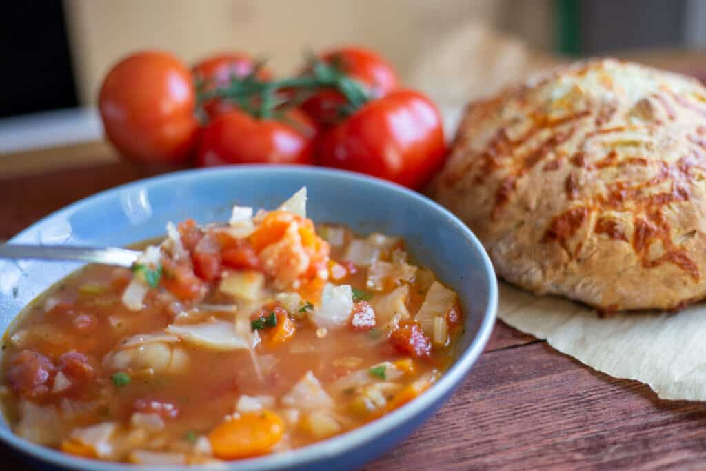 hearty vegetable soup, cheddar & herb soda bread with tomatoes in background sitting on board
