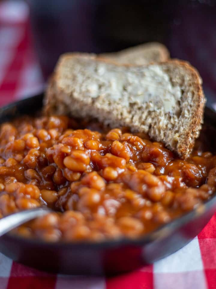 Baked beans in cast iron skillet with buttered bread