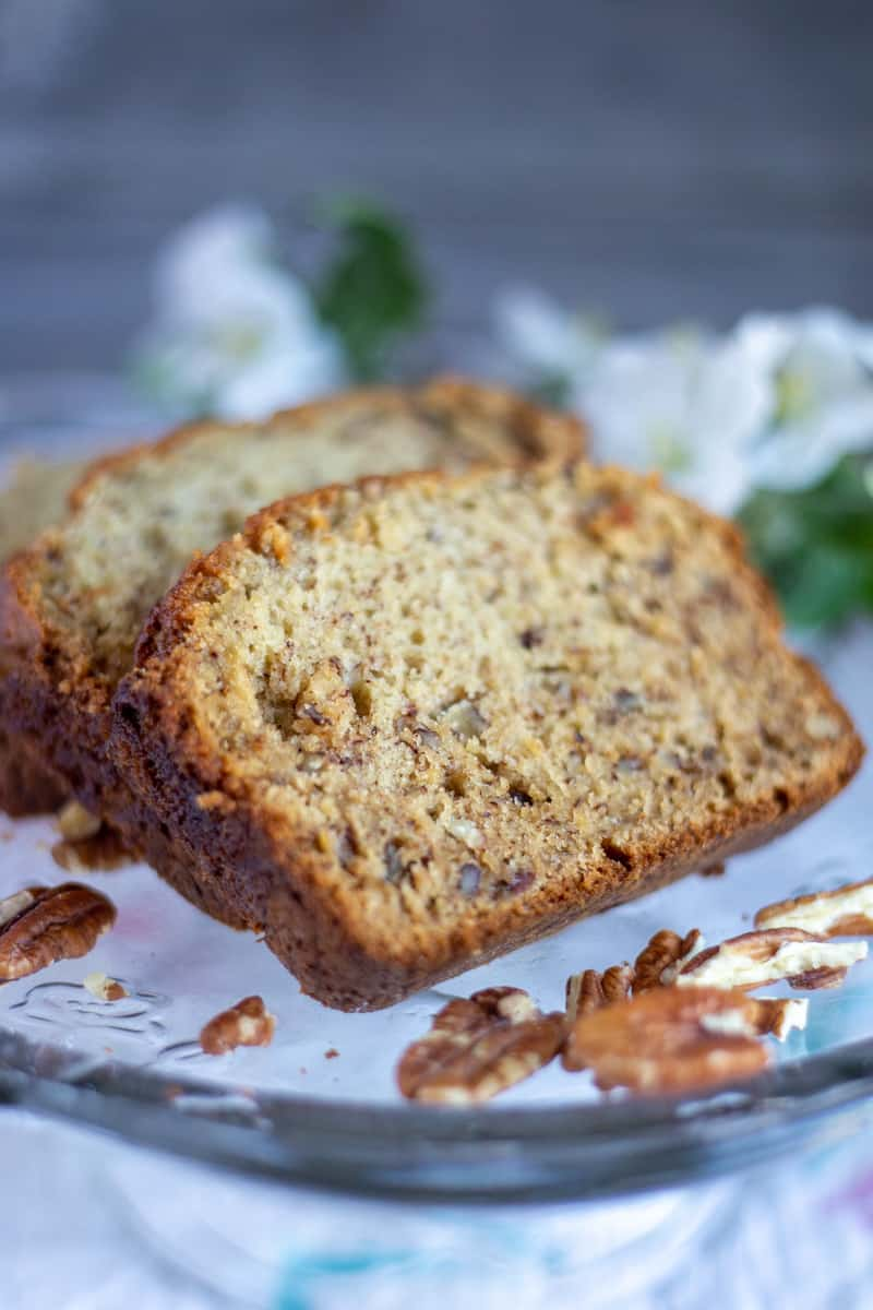 Close up image of sliced banana bread on clear plate.