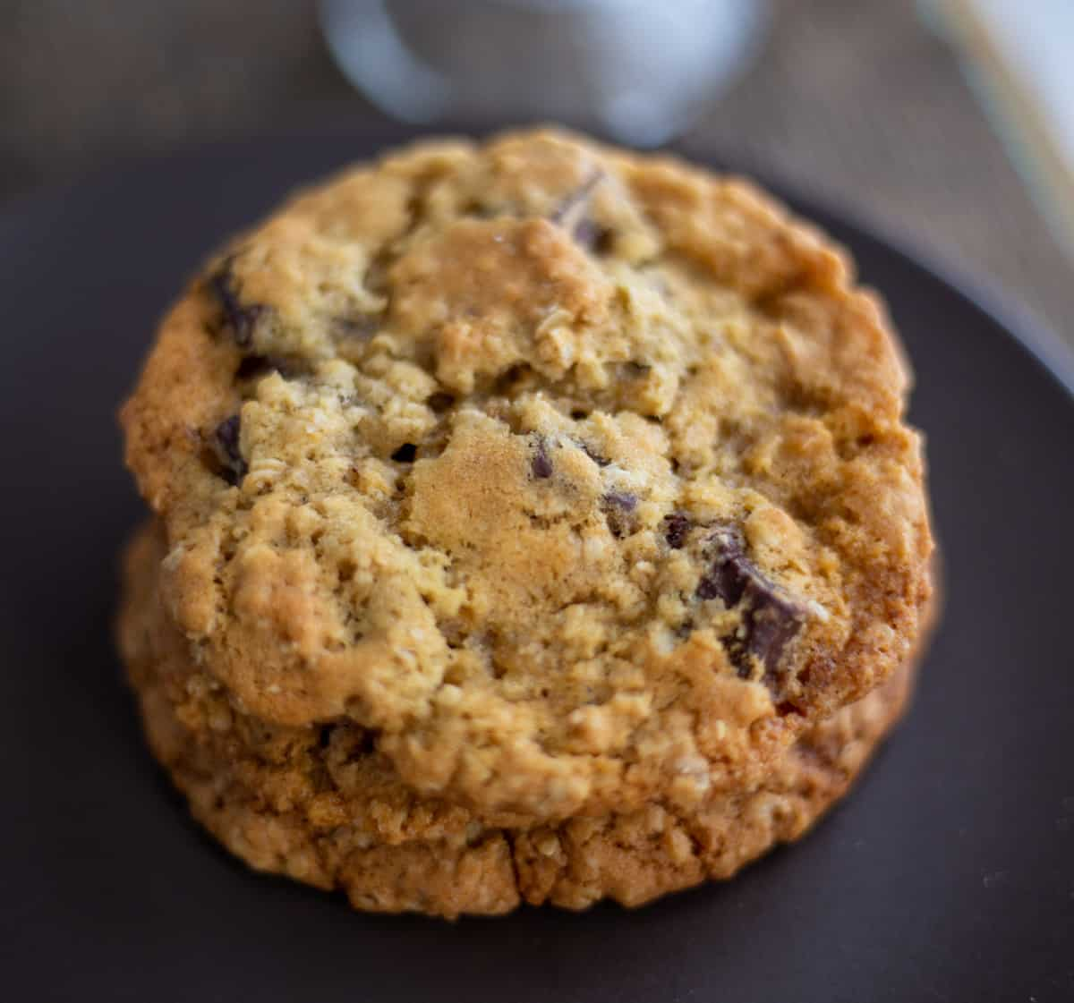 Oatmeal chocolate chunk cookie on brown plate.
