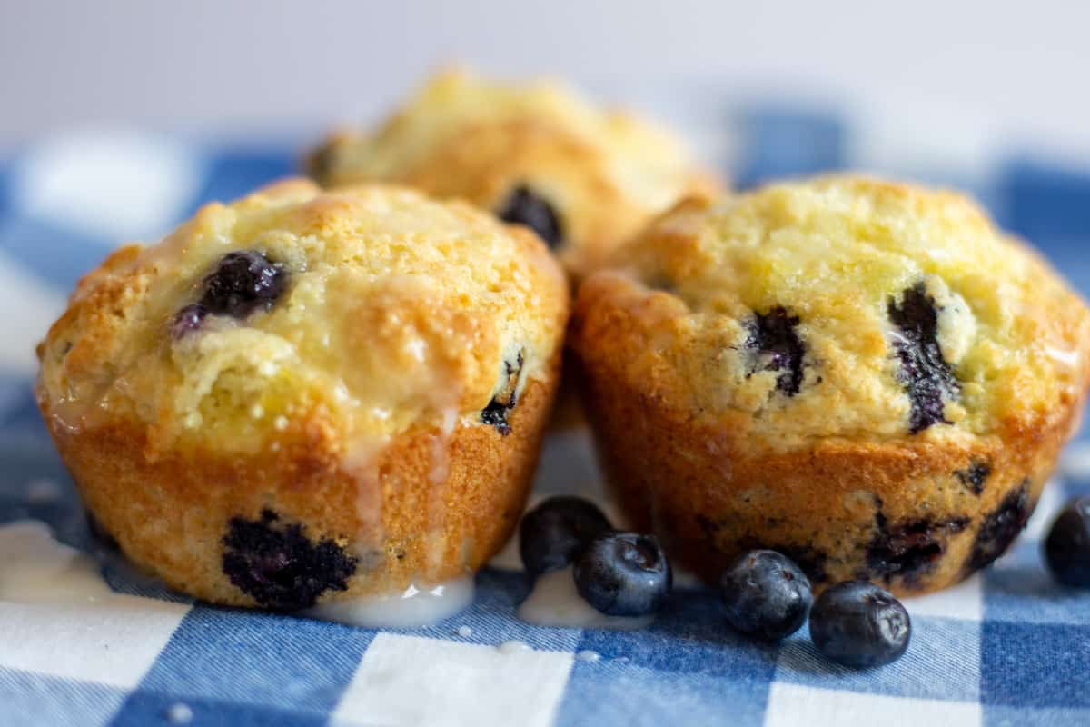 Three lemon blueberry muffins sitting on blue and white napkin.