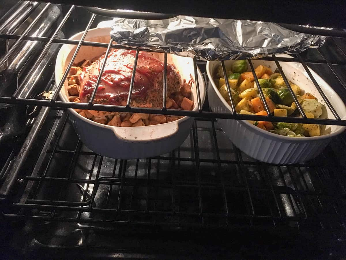 vegetables in white dish baking in oven with turkey breast on bed of stuffing