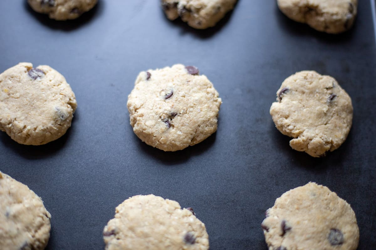 Ubaked oatmeal chocolate chip cookies on baking sheet.