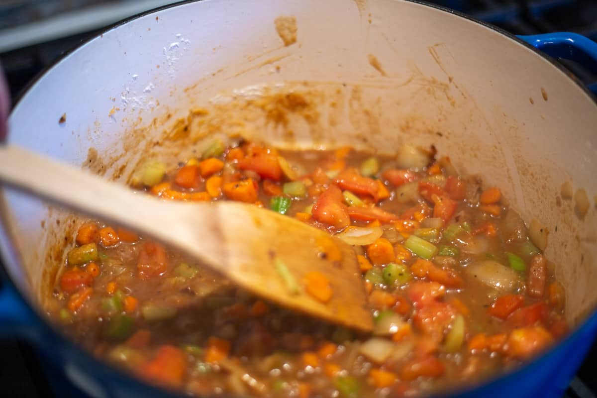 Vegetables thickening with flour and beef broth in Dutch oven.
