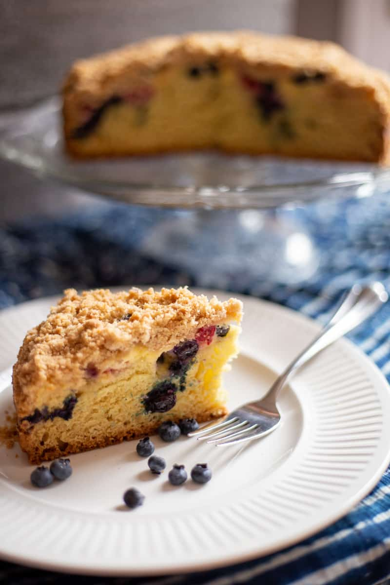 Piece of Blueberry Raspberry Cream Cheese Coffee Cake on white plate with fork.