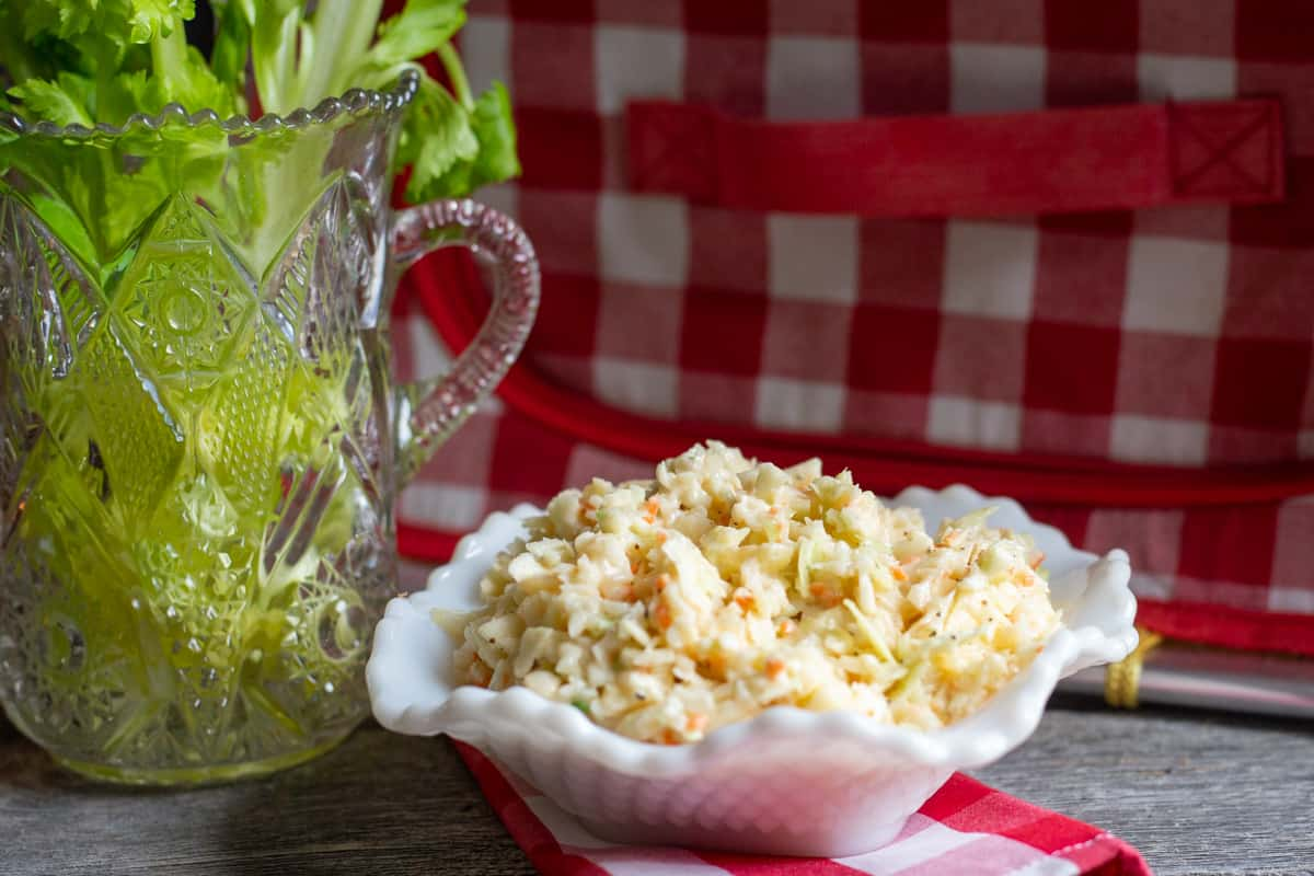 Creamy coleslaw in white dish with celery in background