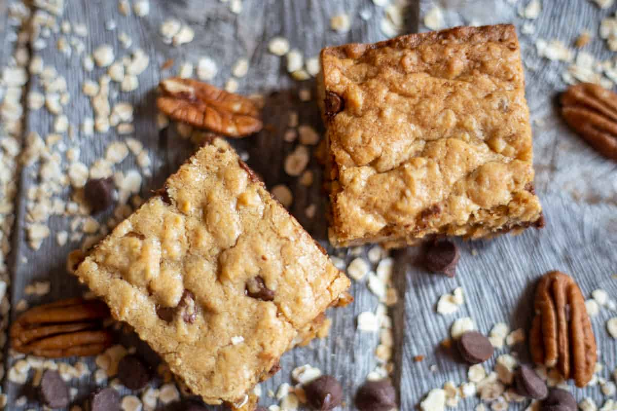 Oatmeal Chocolate chip and peanut butter square on board with loose pecans, oatmeal and chocolate chips
