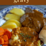 Beef pot roast on a plate with vegetables and gravy.
