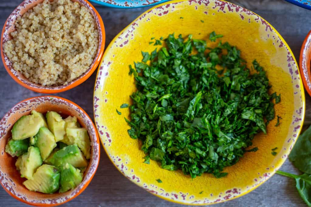 chopped spinach, quinoa, avocado salad in coloured bowls