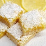 Close up image of lemon bars from scratch on white boards with sliced lemons.