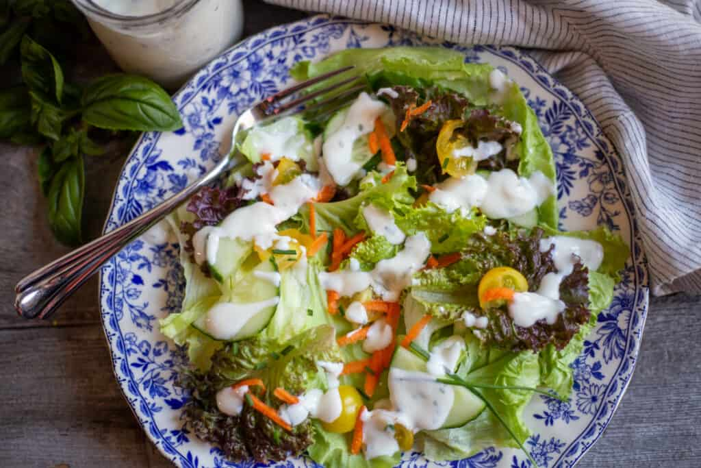 salad on a blue and white plate with fork. Dressed with lemon basil dressing.