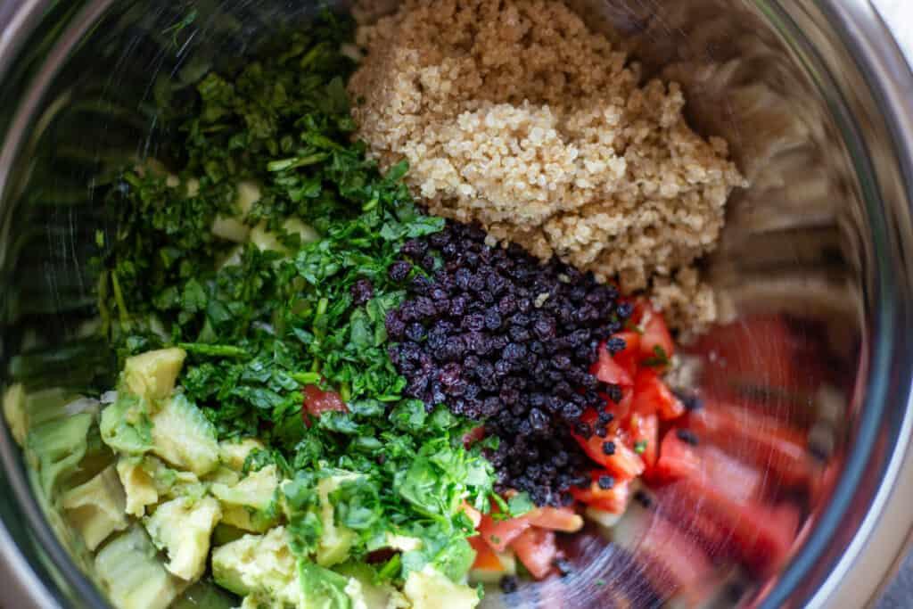 bowl of quinoa, spinach, currants, tomato, avocado