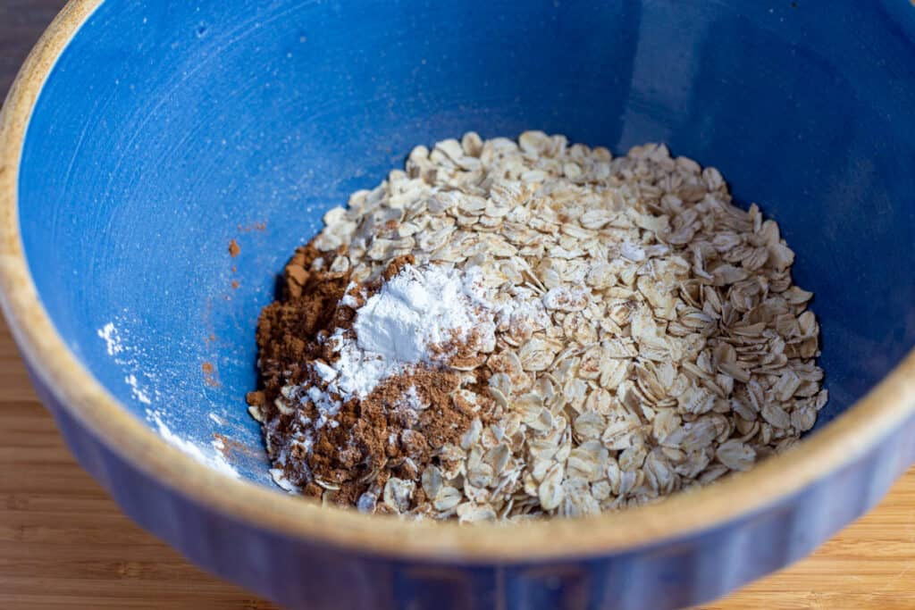 dry ingredients for baked oatmeal in blue ceramic mixing bowl
