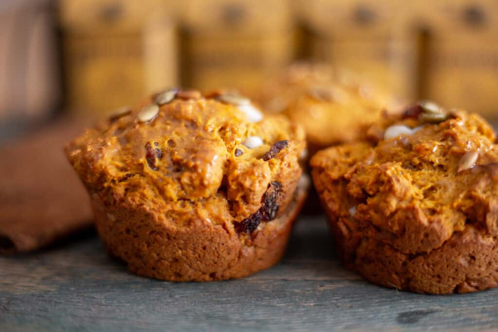 three pumpkin spice muffins with cream cheese sitting on a wooden board