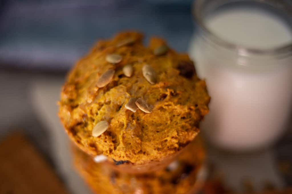 pumpkin spice muffins with cream cheese and glass of milk in background