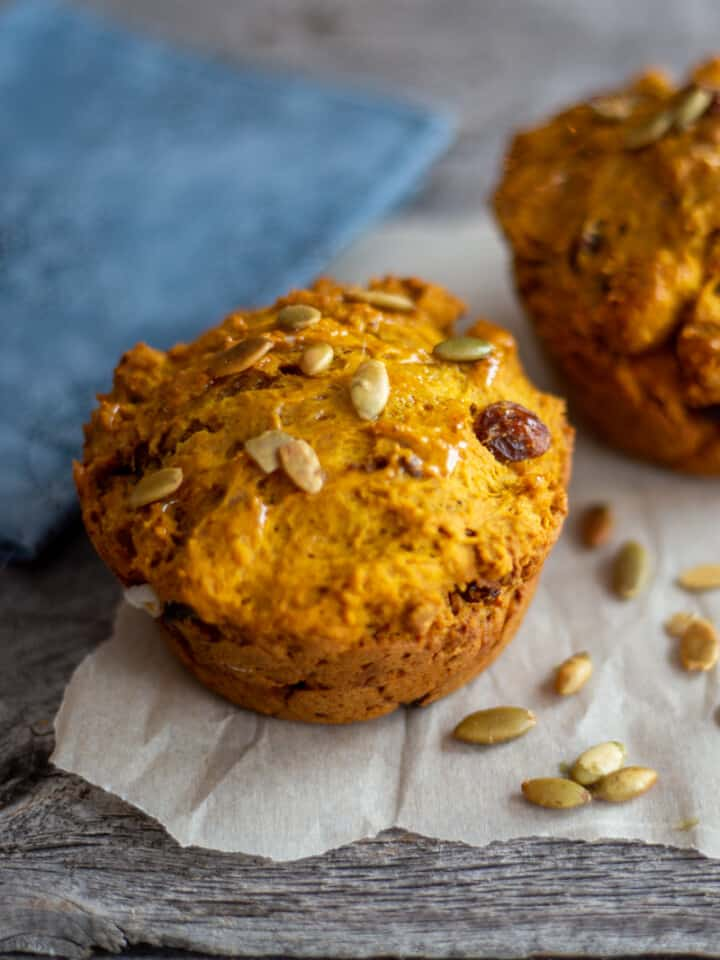 Two jumbo pumpkin spiced muffins on parchment paper with pumpkin seeds scattered