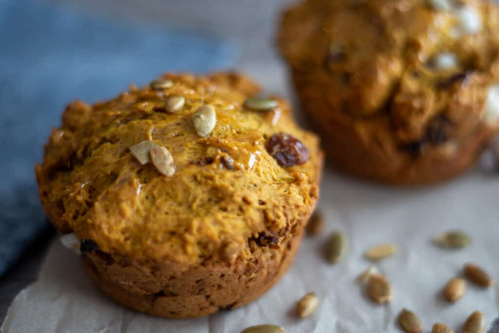 two pumpkin spice muffins with cream cheese on parchment paper surrounded by scatter pumpkin seeds