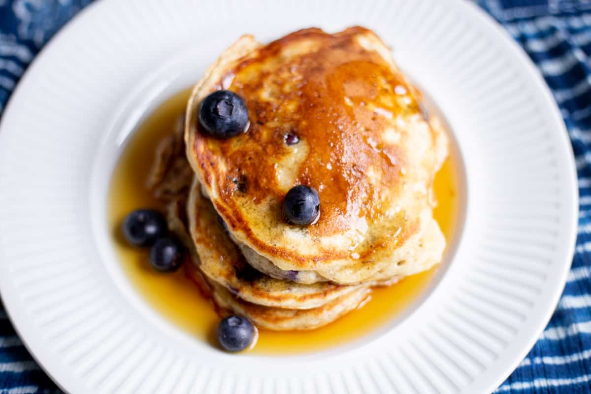 Lemon Blueberry Pancakes with pecans on white plate with maple syrup and blue and white tablecloth in background.