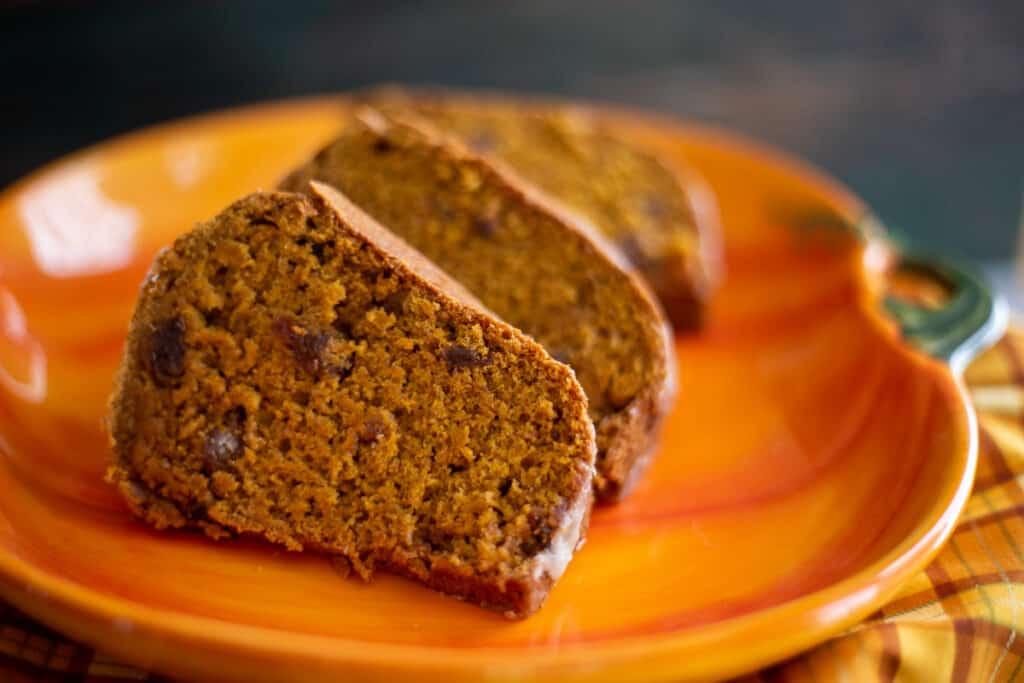 three slices of pumpkin spice bundt cake on orange pumpkin plate