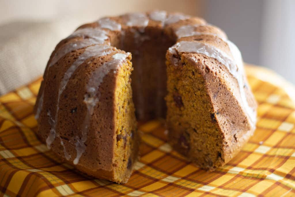 pumpkin spice bundt cake sitting on fall coloured plaid napkin with two slices cut from it