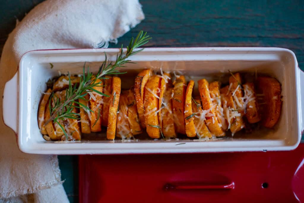 roasted sweet potatoes in casserole dish with sprig of rosemary.