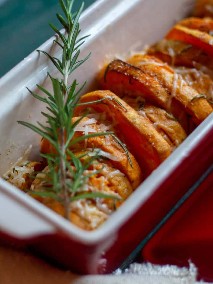 savory roasted sweet potatoes in a red dish with sprig of fresh rosemary