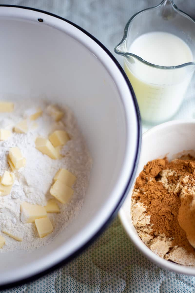 Ingredients for cinnamon buns recipe in mixing bowls and measuring cup.