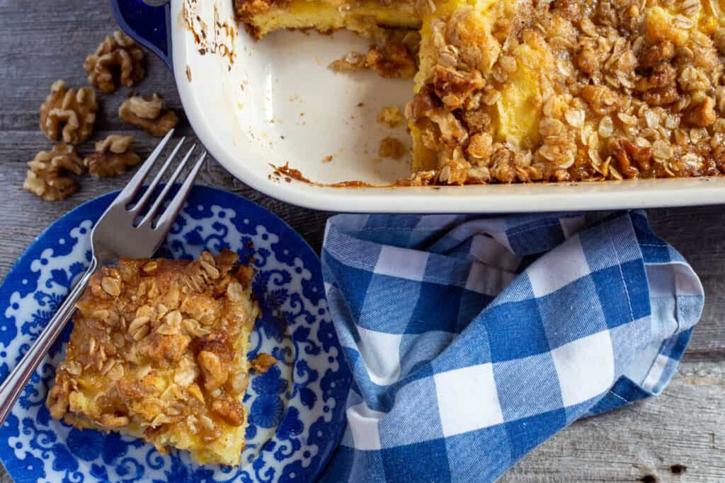 peach streusel coffee cake in blue cake dish and slice on blue and white plate with scattered walnuts on wooden board. Blue and white checkered napkin.