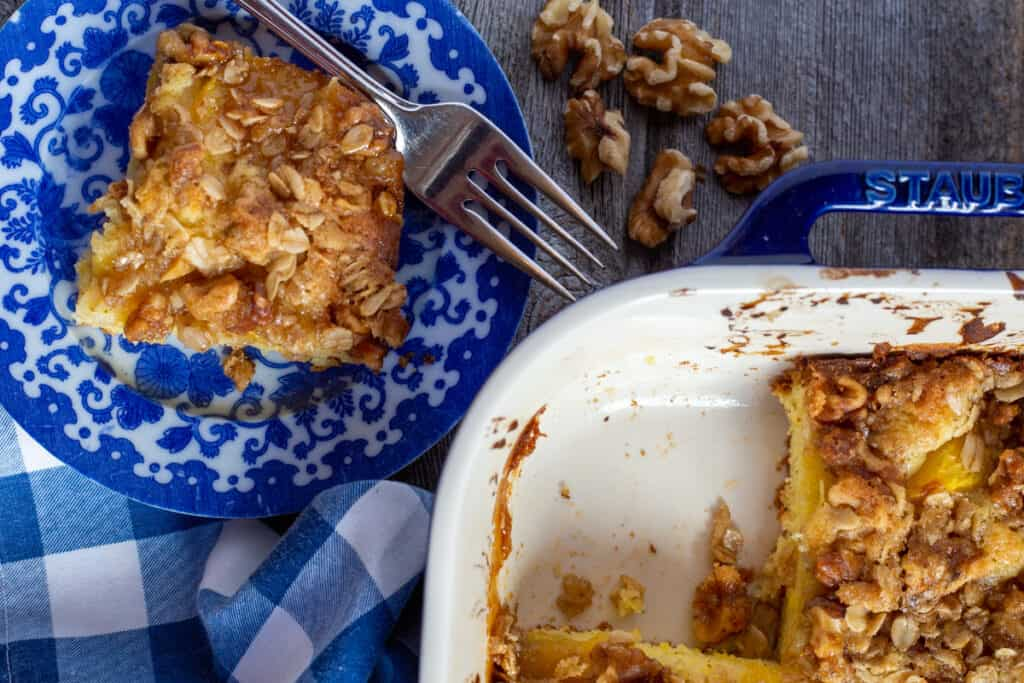 peach streusel coffee cake baked in blue cake dish with slice of cake on plate to the side. Walnuts scattered beside plate and blue and white checkered napkin beside the plate.