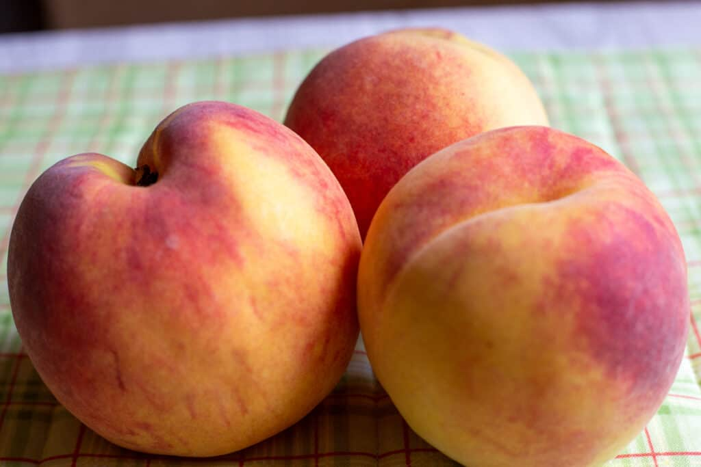 3 large peaches sitting on green cloth