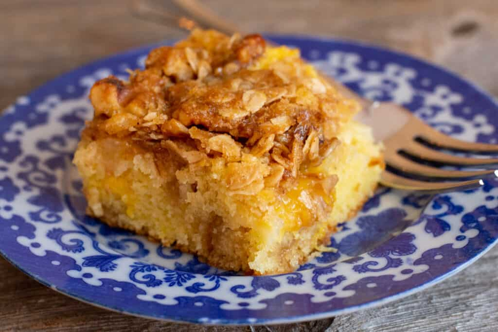 close up of peach streusel coffee cake on blue and white plate