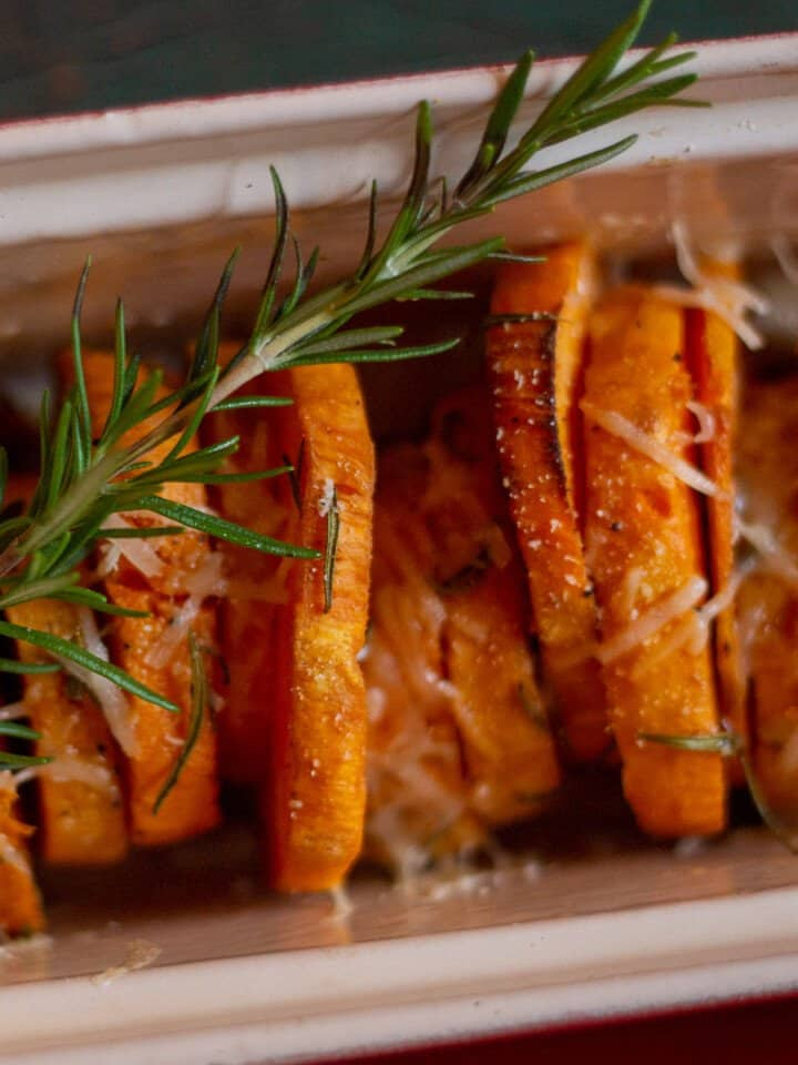 Roasted sweet potatoes in red baking dish with sprig of fresh rosemary.