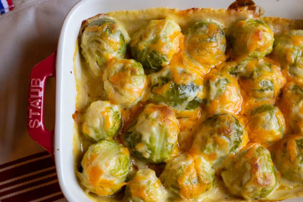 easy cheesy Brussel sprouts in a red casserole dish.