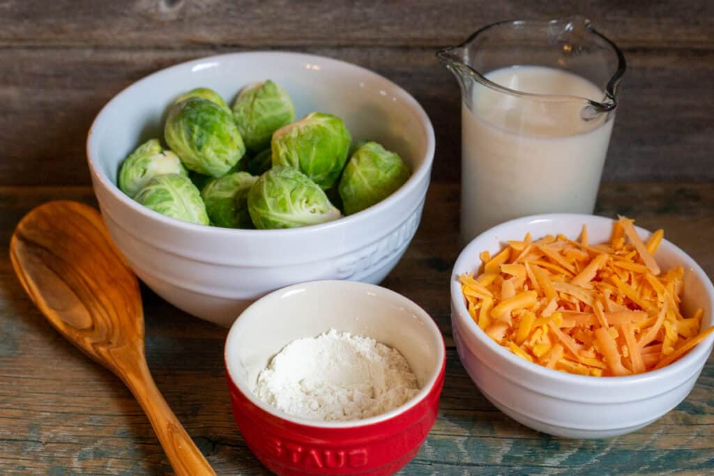 Brussel sprouts uncooked in white bowl. Milk is in glass container beside the Brussel sprouts. In front of the Brussel sprouts is a red dish with flour in it. Next to the red dish is grated old cheddar cheese in a white dish.  To the left of the dishes is a wooden spoon.