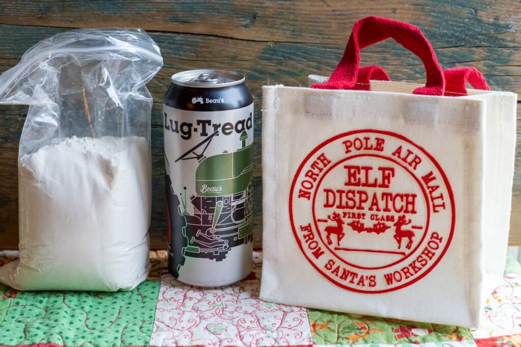 Herbed Beer Bread Mix in a plastic bag with a can of beer beside it. There is a Christmas gift bag bedside the can of beer indicating that they could all be put together as a gift item.