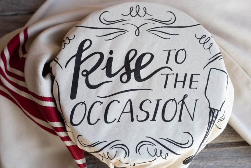 """A beige and red striped tea towel is sitting beside a bowl that is covered in a piece of cloth with the words """"Rise to the Occasion"""" printed on the cloth."""