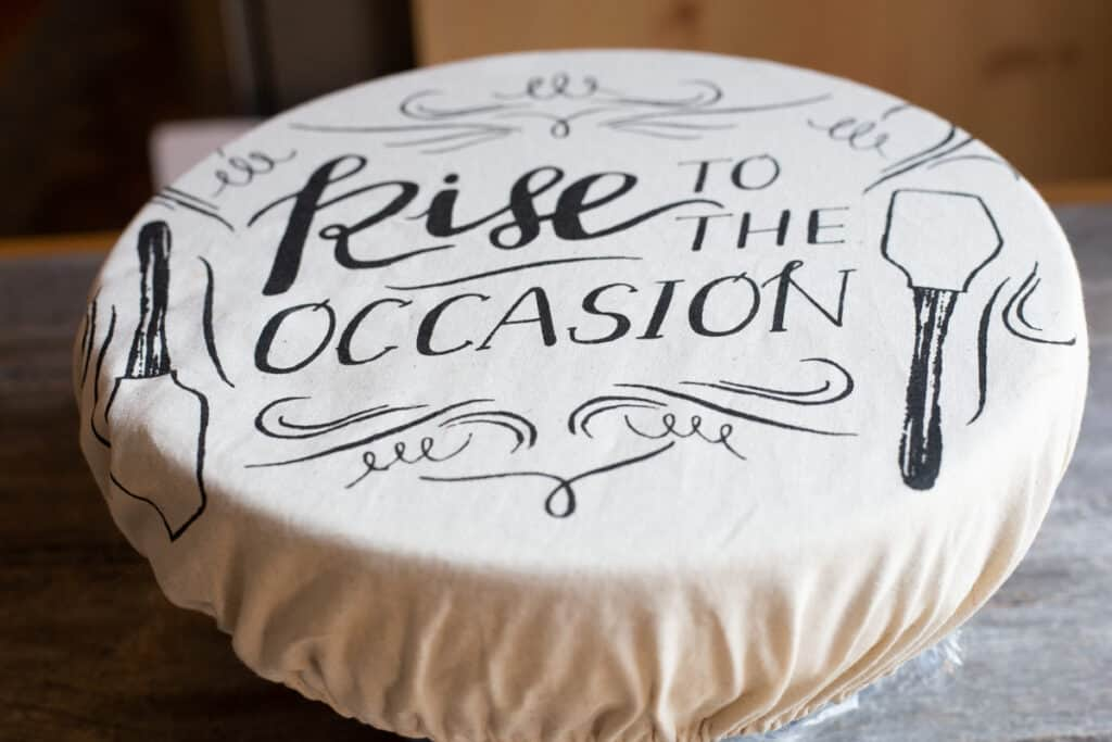 "Artisan dough (not visible) is sitting in a bowl covered with a  cloth that has the writing ""Rise to the Occasion"" written on the cloth. The bowl is sitting on a wooden board."