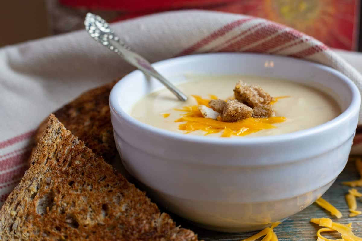 Close up image of Cauliflower Soup in bowl with piece of toasted bread on the side.