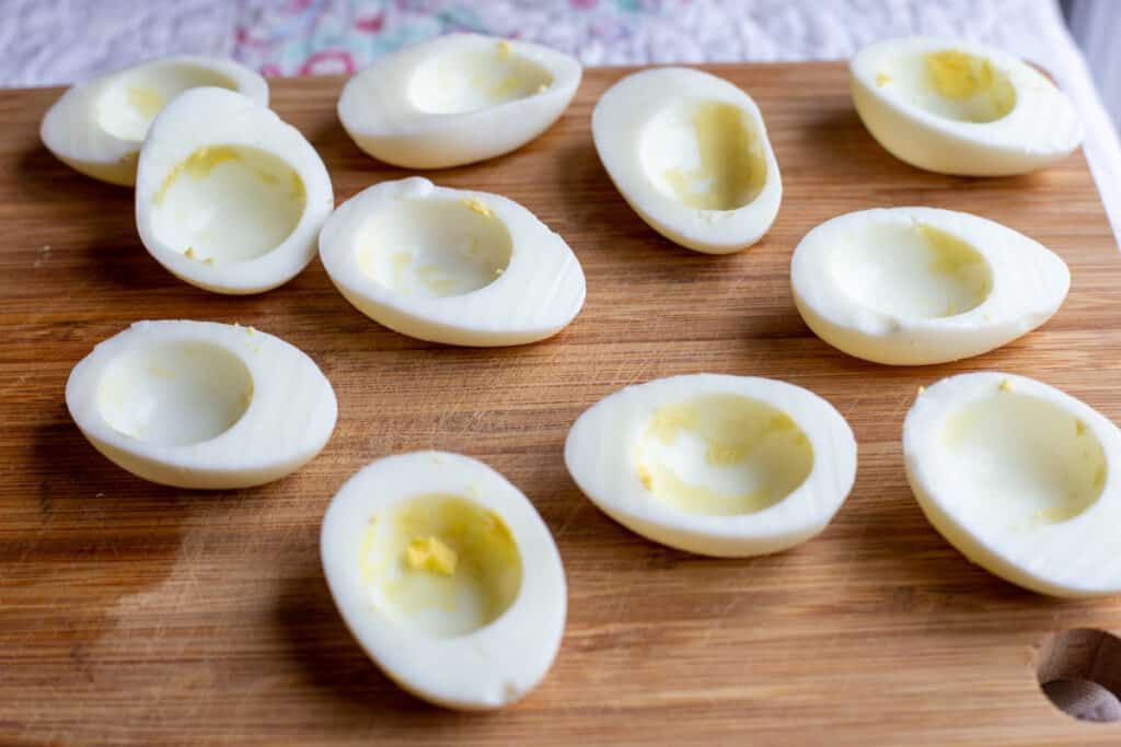 12 hard-boiled eggs cut in half lengthwise are sitting on a wooden cutting board. This is a step in the process of making Devilled Eggs Recipe.