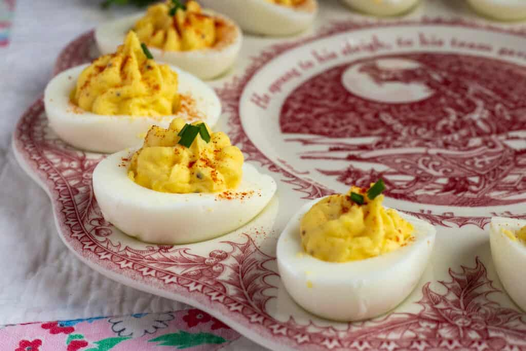 Four devilled eggs sitting on a devilled egg platter. The platter is sitting on a quilt on a table. The devilled eggs are garnished with paprika and chopped chives.