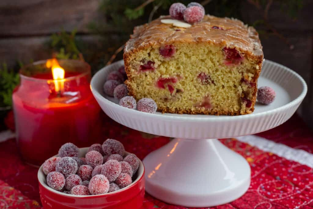 featured image of cranberry orange bread sitting on a white footed plate. A small bowl of sugared cranberries sits to the left of the white plate. A red jar candle flickers in the background.
