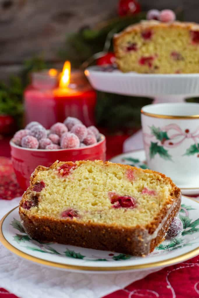 A close up photo of once slice of cranberry-orange bread sitting on a white Christmas plate that has holly and pink ribbon around the edges. A small red bowl with sugared cranberries sits in the background along with a teacup and sauce that matches the holly plate. IN the backgrounders is a footed small cake plate with the remainder of the loaf sitting on it and a red flickering jar candle.