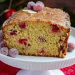 Cranberry Orange Bread with Glaze sitting on a white footed cake plate.