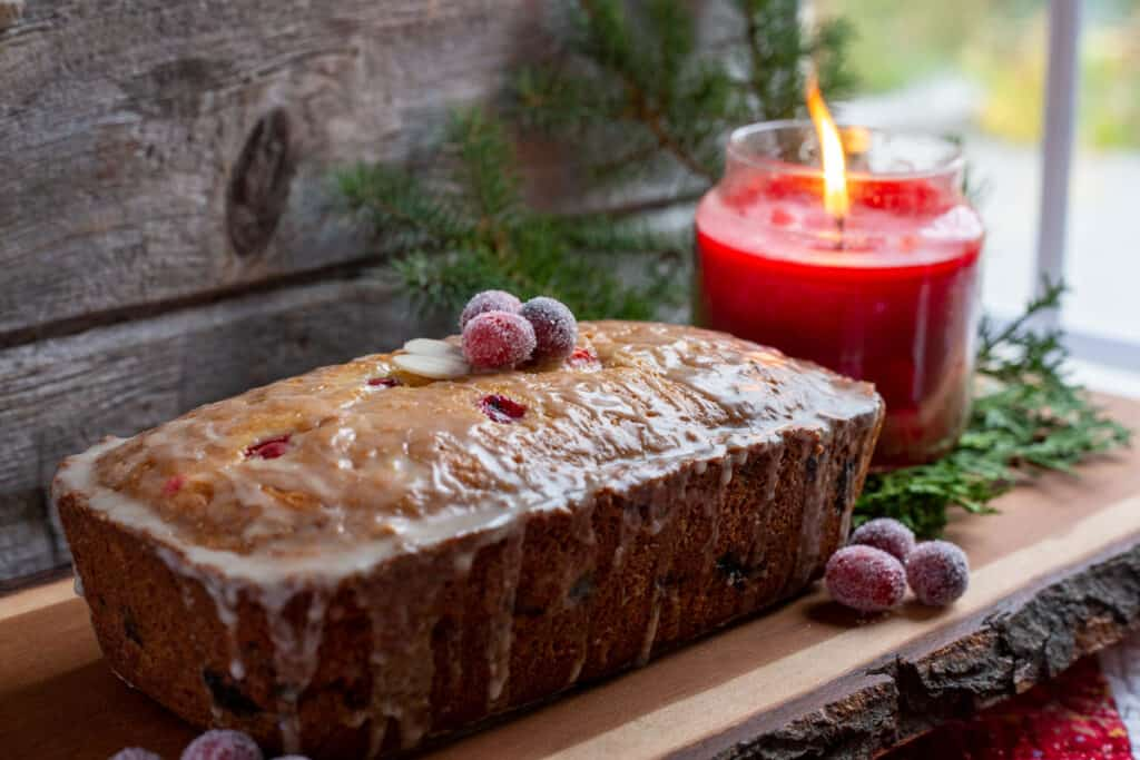 Cranberry Orange Bread with Glaze sits on a wooden charcuterie board. Sugared cranberries sit to the side of the loaf, purely for decorative purposes. In the background is a lit red jar candle that is sitting on a small bed of cut cedar boughs and evergreen boughs.