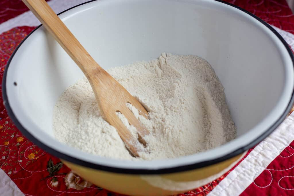 Dry ingredients in a mixing bowl with a wooden spoon for Cranberry Orange Bread with Glaze.